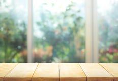 Tampo da mesa de madeira no borrão da janela com fundo da flor do jardim foto de stock