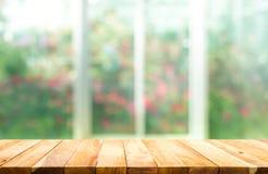 Tampo da mesa de madeira no borrão da janela com fundo da flor do jardim fotografia de stock