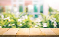 Tampo da mesa de madeira no borrão da janela com fundo da flor do jardim fotografia de stock royalty free