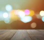 Tampo da mesa de madeira no fundo abstrato com luzes defocused do bokeh Imagem de Stock