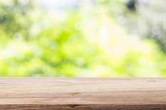 Tampo da mesa de madeira no fundo brilhante do verde do bokeh Para a montagem pro fotos de stock royalty free