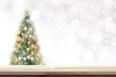 Tampo da mesa de madeira no fundo da árvore de Natal do borrão na queda de neve imagens de stock royalty free