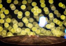 tampo da mesa de madeira no fundo do bokeh da luz da noite do borrão para o displa Fotos de Stock Royalty Free