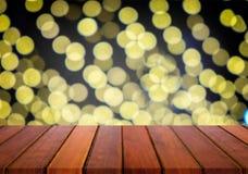 tampo da mesa de madeira no fundo do bokeh da luz da noite do borrão para o displa Fotografia de Stock Royalty Free
