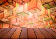tampo da mesa de madeira no fundo do bokeh da luz da noite do borrão para o displa Imagem de Stock