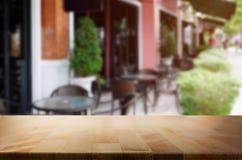 Tampo da mesa de madeira no fundo do borrão da cafetaria & do x28; ou restaurant& x29; Foto de Stock Royalty Free