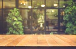 Tampo da mesa de madeira no fundo do café da parede de vidro do borrão imagem de stock royalty free
