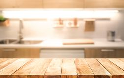 Tampo da mesa de madeira no fundo da sala da cozinha do borrão que cozinha o conceito