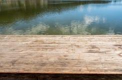 Tampo da mesa de madeira no lago natural Fotos de Stock Royalty Free