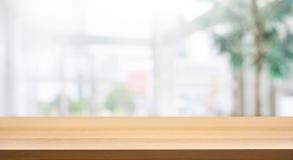 Tampo da mesa de madeira no prédio de escritórios branco do formulário do fundo da parede de vidro do borrão imagens de stock