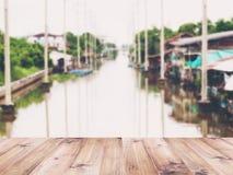Tampo da mesa de madeira sobre o fundo abstrato do borrão da casa do beira-rio do vintage em Tailândia foto de stock royalty free