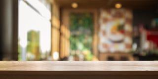 Tampo da mesa de madeira vazio com a cafetaria ou o restaurante do borrão inter fotografia de stock royalty free