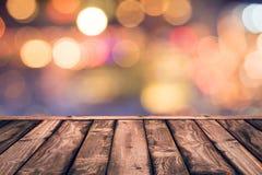 Tampo da mesa de madeira vazio com fundo borrado do sumário do bokeh das luzes Foto de Stock Royalty Free