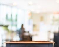 Tampo da mesa de madeira vazio com fundo da loja do borrão, zombaria do molde imagens de stock royalty free