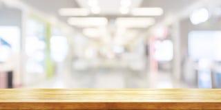 Tampo da mesa de madeira vazio com fundo moderno borrado do shopping Bandeira panorâmico fotografia de stock
