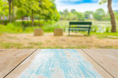 Tampo da mesa de madeira vazio com o banco borrado no fundo do jardim Fotos de Stock