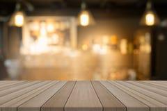 Tampo da mesa de madeira vazio na cafetaria borrada do formulário do fundo imagens de stock