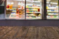 Tampo da mesa de madeira vazio no fundo borrado do supermercado na noite imagens de stock royalty free
