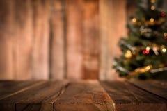 Tampo da mesa de madeira velho com a árvore de Natal do borrão no fundo imagem de stock royalty free
