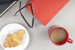 Tampo da mesa de um leitor que toma uma ruptura de café Fotografia de Stock Royalty Free