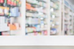 Tampo da mesa do contador da loja da farmácia com medicina do borrão em prateleiras Fotos de Stock