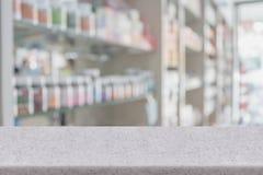 Tampo da mesa do contador da loja da farmácia com medicina do borrão em prateleiras fotografia de stock royalty free