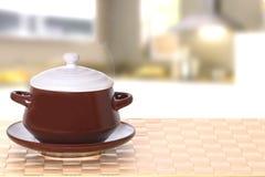Tampo da mesa no fundo da bacia Close up da bacia de sopa cerâmica marrom quente na placa com tampa em uma toalha de mesa brilhan imagens de stock royalty free