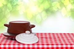 Tampo da mesa no fundo da bacia Bacia de sopa cerâmica marrom vazia na placa com tampa em uma toalha de mesa quadriculado vermelh imagens de stock