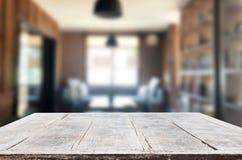 Tampo da mesa vazio da placa de madeira e para borrar interior sobre o borrão no coff imagem de stock royalty free