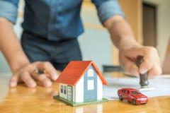 Tampon en caoutchouc d'utilisation d'hommes sur le papier, la maison modèle et la voiture modèle garés Photographie stock libre de droits