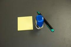 Tampon en caoutchouc rond moderne, bloc-notes collant jaune et stylo Image stock
