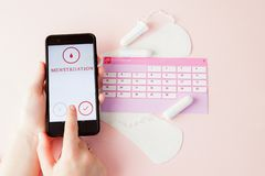 Tampon, feminine, sanitary pads for critical days, feminine calendar, pain pills during menstruation on a pink background. Tracking the menstrual cycle and stock image