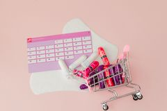 Tampon, feminine, sanitary pads for critical days, feminine calendar, pain pills during menstruation on a pink background. Tracking the menstrual cycle and royalty free stock images