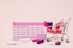 Tampon, feminine, sanitary pads for critical days, feminine calendar, pain pills during menstruation on a pink background. Tracking the menstrual cycle and stock photos