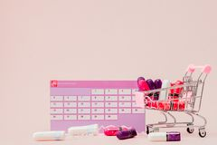 Tampon, feminine, sanitary pads for critical days, feminine calendar, pain pills during menstruation on a pink background. Tracking the menstrual cycle and stock photography