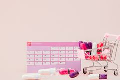 Tampon, feminine, sanitary pads for critical days, feminine calendar, pain pills during menstruation on a pink background. Tracking the menstrual cycle and royalty free stock photos