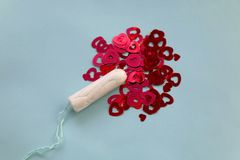 Tampon. With red heart shaped sequins symbolizing menstruation. Top view, light blue background royalty free stock image