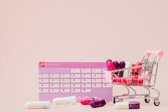 Tampon, vrouwelijke, sanitaire stootkussens voor kritieke dagen, vrouwelijke kalender, pijnpillen tijdens menstruatie op een roze stock fotografie
