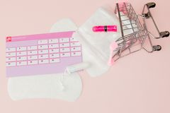 Tampon, vrouwelijke, sanitaire stootkussens voor kritieke dagen, vrouwelijke kalender, pijnpillen tijdens menstruatie op een roze royalty-vrije stock foto's