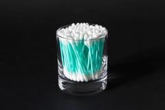 Tampons de coton dans le pot en verre clair sur le fond noir Photos stock