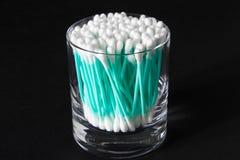 Tampons de coton dans le pot en verre clair sur le fond noir Image stock