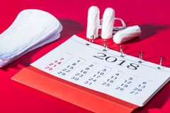 Tampons, daily pads and calendar. On red stock images