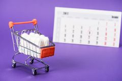 Tampons in small shopping cart and calendar. On purple Royalty Free Stock Image