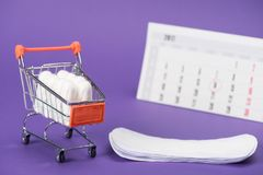 Tampons in small shopping cart, daily liners and calendar. On purple royalty free stock image