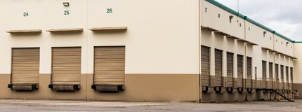 Tan and brown warehouse industrial building and garage doors stock photography