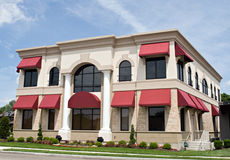 Tan Building with Red Awnings Royalty Free Stock Photos