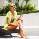 Tan-Frau, die Sonnenschutzlotion nahe einem Swimmingpool anwendet Stockfotografie