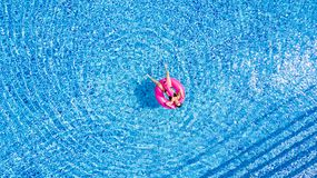Tan girl sits on inflatable mattress flamingos in the pool from above stock images