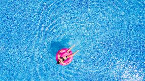 Tan girl sits on inflatable mattress flamingos in the pool from above royalty free stock image