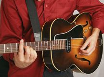 Tan and gold acoustic guitar. Played left handed, by male musician wearing a red shirt Stock Image